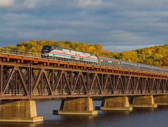 The Amtrak Autumn Express crosses the Hudson River in Mechanicville, New York, the fall colors in full bloom. | Photo by Amtrak / Marc Glucksman