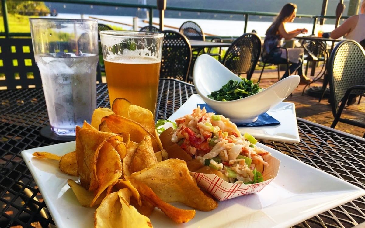 A lobster roll, served with old bay chips and an additional side of sautéed kale. Don't forget the cold pint of Ommegang Rare Voss! | Photo by Andrew Frey