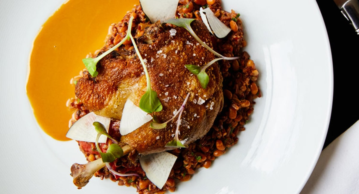 The duck confit from Fazio Farms. Plated over Jefferson red rice perloo with radish and an oyster dressing. | Photo from Wm Farmer and Sons